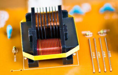 Détail du transformateur à noyau de ferrite magnétique sur une carte de circuit imprimé beige. Close-up de bobines d'induction avec enroulement de fil de cuivre. Composants électroniques en électrotechnique. Appareil électrique démonté.