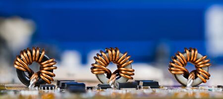 Fond électrotechnique panoramique. Inductances toroïdales avec un beau bobinage en fil de cuivre. Composants électroniques comme des bobines ou des transistors sur le détail de la carte de circuit imprimé. Copiez l'espace sur un appareil bleu flou. Banque d'images