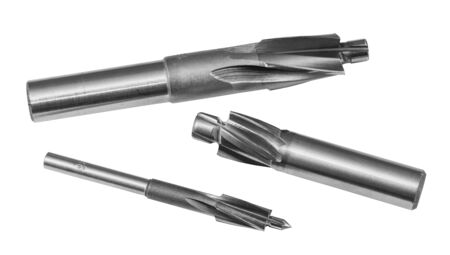 Three steel cylindrical counterbores isolated on white background. Sharp cutting tools set for drilling counterbored coaxial holes. Detail of spiral fluted cutters. Metal equipment for chip machining.