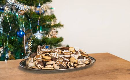 Decorated green Christmas tree and silvery tray with various sweet cookies on a wood table. Pile of ornate confections. Still life with Xmas and New Year mood and copy space on empty white background. Stok Fotoğraf
