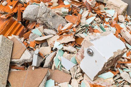 Détail de la décharge de déchets de construction. Tas de gravats de briques cassées, de tuiles et de béton. Gros plan des débris de construction. Morceaux de plancher et de maçonnerie endommagés. Idée de rénovation ou de démolition, d'explosion et de tremblement de terre.