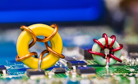 Two colored toroidal induction coils on green circuit board detail. Round magnetic core inductors with copper wire winding. Electronic components on blue electrotechnical background. Selective focus.