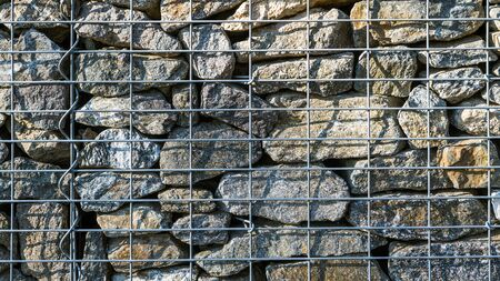 Gabion retaining wall texture. Closeup of stacked stones in wire mesh cage. Background of protective fence detail made from sunlit gray pieces of rocks in a metal grid with shadows on boulder masonry.