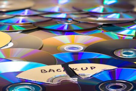 Shredded optical compact disc parts on heap of colored archiving media. Obsolete data storage device for secure backup. Disposal of secret digital files. Old archive disks with green-blue reflections.