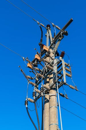 Medium voltage disconnectors on electricity pylon against a blue sky. Concrete pole with isolator switches used to disconnect of electrical circuit for safe service, maintenance, adjustment or repair.