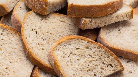 Brown bread pile detail. Half slices as side dish portions. Staple food. Culinary background from many slabs of sliced crunchy loaf. Rustic texture of salty baked product from wheat flour with crust.