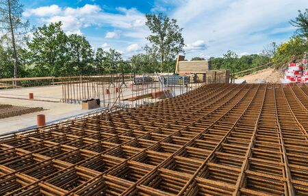 Reinforcing bars grid for ferroconcrete. Building foundations in green trees. Rebar mesh of rusty steel wires for reinforced concrete and masonry on construction site under blue sky with white clouds. Stok Fotoğraf