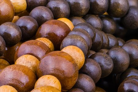 Round wooden strung beads tangled in pile as beautiful artistic background. String detail of beige and brown painted balls of various size from natural lacquered wood. Texture in harmonic color tone.