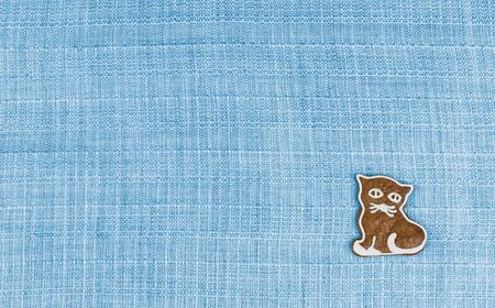 Cute gingerbread kitty-cat on blue textile background with grid texture. Sweet hand painted baked kitten on decorative fabric. Concept of Childrens Day greeting card or invitation to child party. Stok Fotoğraf