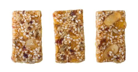 Three sweet shortcrust biscuits glazed by honey coating isolated on white background. Set of yummy rectangular cookies full of sliced almonds, dried fruits, sesame and sunflower seeds or raisins.