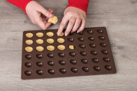 Filling raw shortcrust biscuit dough into silicone baking mold on wood background. Female hands detail when making traditional sweets in nuts shape. Flat brown pastry form on kitchen table.
