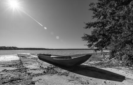 Small boat on pond shore. Artistic black and white scene. Natural still life. Fishing vessel on concrete pier, tree, rippled water surface and sunbeams on sky above horizon. Czech Horusicky fishpond. Stok Fotoğraf
