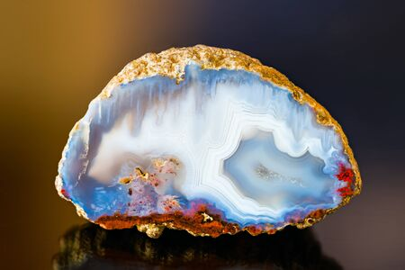 White blue agate gem cross section with reflection on dark colored background. One natural quartz chalcedony detail with crystals in a small geode. Red spots on smooth polished surface. Ice like look. Stok Fotoğraf