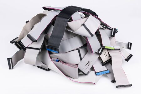 Flat multi wire ribbon cables pile isolated on white background. Internal parallel bus connectors for data storage devices attachment such as optical or hard disk. Old spare parts. E-waste separation.