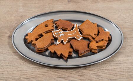 Cute white decorated gingerbread cat and mix of stacked cookies on silvery plate. Sweet holiday biscuits of varied shapes in shiny round platter on wooden background. Xmas, Childrens or Cat Day. Stok Fotoğraf