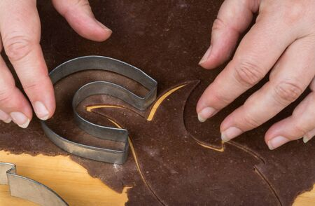 Metal cookie cutter on gingerbread dough and female hands. Cutting out of horseshoe shaped Christmas sweets from rolled raw pastry on wood board. Detail of baking traditional scented Xmas decorations. Stok Fotoğraf