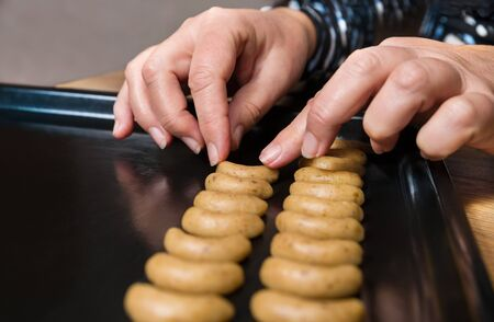 Female hands placing vanilla crescent roll cookies dough on black baking tray. Close-up of shaping traditional Czech Christmas and wedding nutty biscuits on sheet pan. Making of sweet fragrant pastry. Stok Fotoğraf