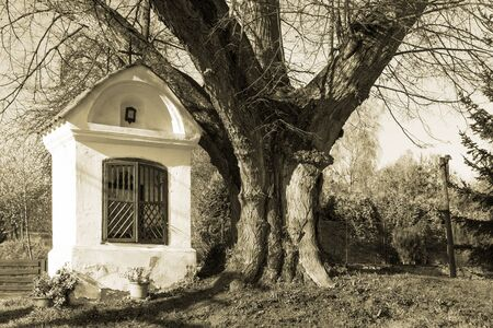 Vintage roofed column wayside shrine near old tree trunk. Sepia toned background. Small Christian religious chapel with window and niche in tranquil rural scene. Jistebnice city on Czech countryside.