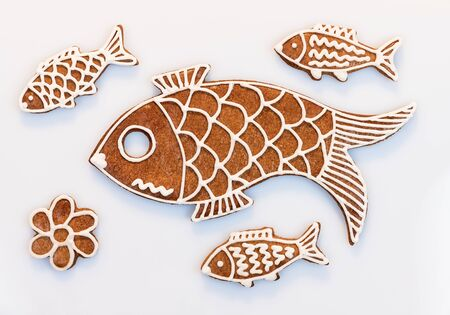 Cute hand painted gingerbread fish cookies on white background. Group of ornate traditional Christmas or New Year sweets. Aromatic baked little or big fishes. Set of Xmas pastries decorated by icing.