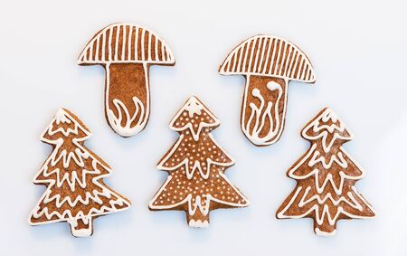 Ornate Christmas gingerbreads in tree or mushroom shape on white background. Set of traditional baked Xmas and New Year decorations closeup. Group of cute aromatic cookies decorated by sugar frosting.