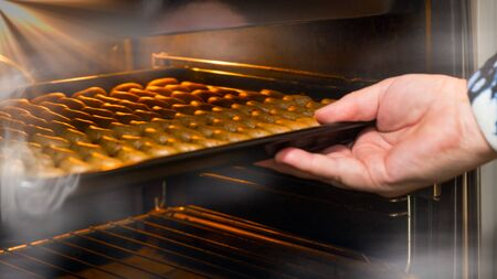 Female hand putting baking tray with vanilla rolls to open hot steaming oven. Stacked crescent shaped raw sweets on lit flat sheet pan. Traditional Czech Christmas or wedding cookies from nutty dough.