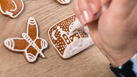 Decorating Christmas gingerbreads close-up. Female hand painting a church on cookie. Woman with pastry bag of sweet white icing. Making of ornate aromatic baked biscuits. Traditional Xmas decorations. Stok Fotoğraf