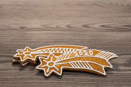 Ornate gingerbread Bethlehem star. New Year 2020. Gold sweets for happiness. Aromatic baked Xmas cookies decorated by white icing. Stacked golden biscuits for good luck. Still life on wood background.