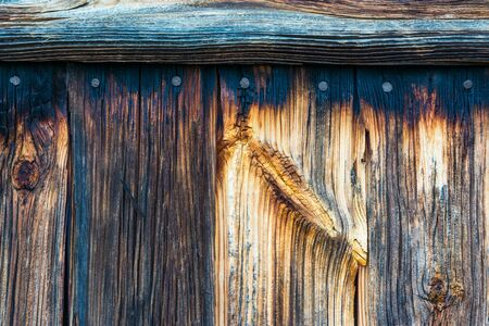 Old rustic wooden textured planks. Closeup of an ancient weathered construction. Detail of faded wood with knots, nails and a horizontal batten. Abstract vintage background with rough cracked surface. Stok Fotoğraf