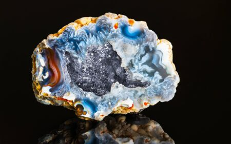 Beautiful hollow agate semi-precious stone with clear raw crystals inside geode. One natural chalcedony with blue colored cut surface and crystalline crystal in cavity detail. Quartz of north Bohemia.