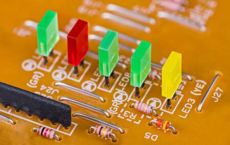 Colored rectangular light-emitting diodes in row on printed circuit board detail. Close-up of green, red and yellow plastic LED lights, small resistors and jumper wires on beige PCB. Electrotechnics.