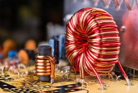 Bobinage de fil de cuivre d'inducteur. Composants électroniques soudés dans le circuit imprimé. Bobines d'induction toroïdales et cylindriques. Détail de l'unité d'alimentation de l'ordinateur démonté. Réflexion sur radiateur en aluminium.