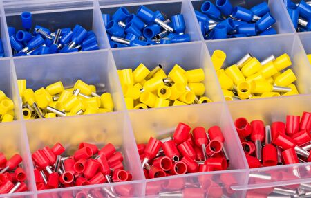 Ferrule pin cord end terminals kit detail arranged in grid of plastic box. Insulated wire copper crimp connectors organized in toolbox. Colored crimping equipment for permanent electric cable joining.