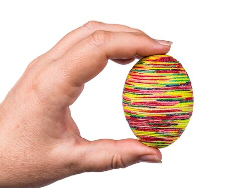 Female hand holding multicolored golden Easter egg shell isolated on white background. Traditional holiday ornate empty chicken eggshell decorated by glued thin twine painted by various bright colors.