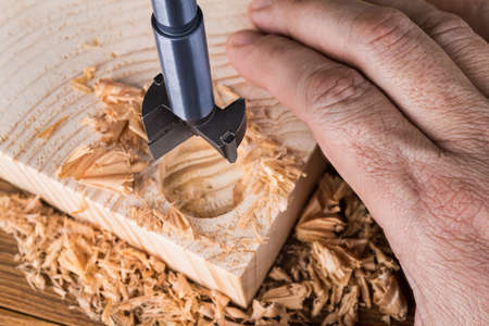 Forstner drill bit detail. Craftsman boring cylindric hole into wood. Hand of joiner on wooden plank, sharp steel cutting tool and scattered shavings. Precise drilling of flat-bottomed bore. Woodwork.