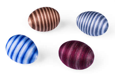 Four decorative streaked Easter eggs on white background. Close-up of blue, red or brown colored egg shells decorated with glued cotton sewing thread. Original holiday decoration from empty eggshells. Zdjęcie Seryjne