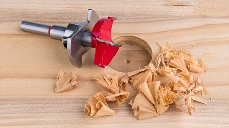 Forstner drill bit. Steel cutting tool for boring precise flat-bottomed holes. Red milling cutter with positioning plate. Drilled cylindrical bore and spiral shavings on wooden plank detail. Woodwork.