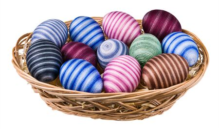 Striped hand-decorated Easter eggs in wicker basket isolated on white background. Colored empty eggshells wrapped by pasted cotton sewing thread. Traditional holiday decoration from ornate egg shells.