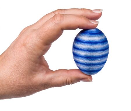 Blue striped Easterr egg in female fingers isolated on white background. Human hand closeup holding original holiday decoration coated by thin yarn. Chicken eggshell decorated with glued cotton fiber.