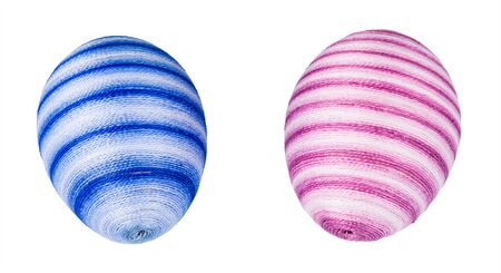 Ornate holiday Easter eggs streaked in soft blue or pink color isolated on white background. Close-up of two original decorations. Beautiful egg shells hand-decorated with glued sewing cotton thread.
