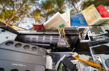 Electronic waste detail. Computer hardware components on pile under trees. Close-up of used plastic and metal PC parts in nature. Monitor, keyboards, mainboards or power socket. Eco, carbon footprint.