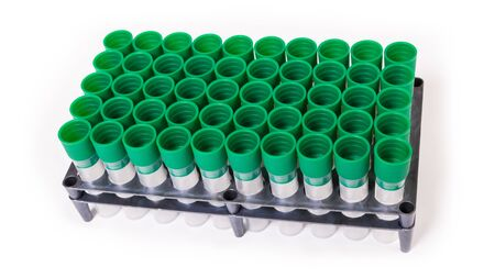 Empty laboratory test tubes in plastic rack on white background. Medical sample tube with green screw cap. Sterile diagnostic equipment of hospital or hematology blood transfusion center. Health care. Stock Photo