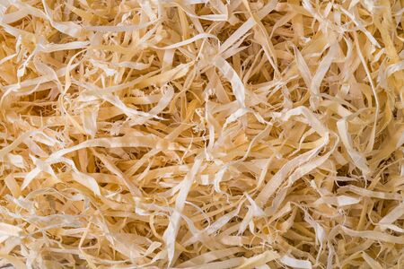 Abstract wood shavings background. Wooden sawdust in texture detail. Closeup of long thin strips of woodworking waste tangled on pile. By-product of planing, milling or drilling. Carpentry or joinery.