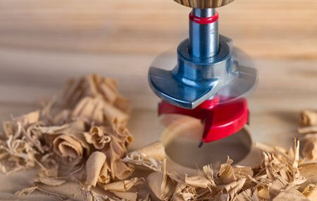 Steel Forstner drill bit with locking plate. Boring of cylindrical hole into wooden plank. Artistic still life with beautiful motion blur of drilling tool, round drilled bore and spiral wood shavings. Stock Photo