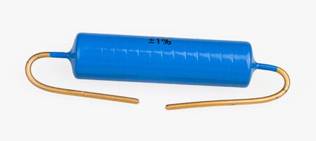 Blue metallized power electronic resistor with gilded terminal wires on white background. One passive electric component. Use in printed circuit board. Electrical resistance. Electrotechnics industry.