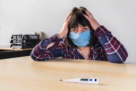 Sick woman with coronavirus disease and blue protective mask on face. Covid-19 pandemic outbreak. High fever on medical thermometer on table. Headache and panic fear in quarantine at home office work.