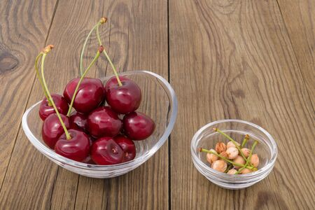 Pile of juicy red cherries with green stems in glass bowl on wooden background. Prunus avium. Closeup of yummy sweet ripe fruits and cherry pits in small round dish on brown wood. Vegetarian raw food.