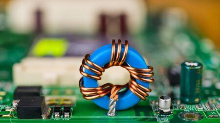 Bobine d'induction toroïdale bleue sur circuit imprimé vert. Détail de la carte mère de l'ordinateur. Composants electroniques. Inductance à noyau de ferrite, condensateur, transistor ou diode. Arrière-plan flou, bokeh. Mise au point sélective.