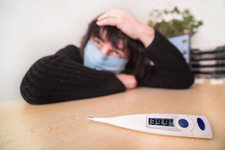 Coronavirus disease. Sick woman with face mask. High body temperature on medical thermometer. Covid-19 outbreak. Fever, head and throat pain. Panic fear of pandemic viral infection in home quarantine.