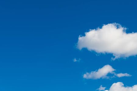 Clear azure blue sky background with group of romantic puffy white clouds. Abstract airy cloudscape in sunny wheather. Empty space and sunlit floating cumuli. Meteorology, ecosystem or climate change. Stock Photo