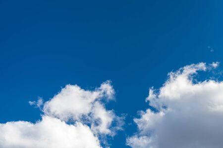 Sunlit blue sky background with copy space and group of white precipitation clouds. Scenic natural view on dramatic airy cloudscape and flowing puffy cumulus. Ecosystem, water cycle or climate change.
